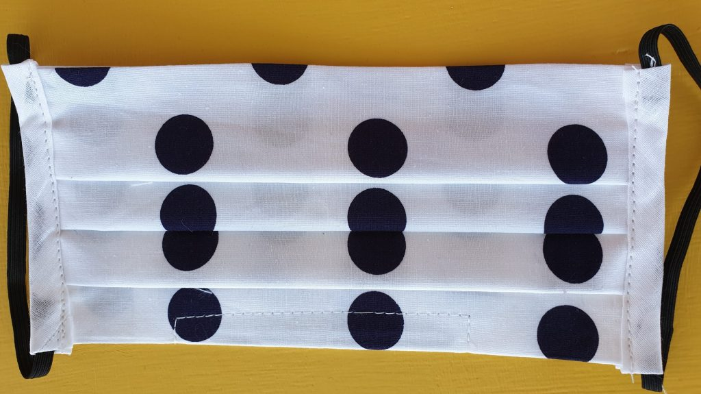 White face covering with large dk navy pola dots