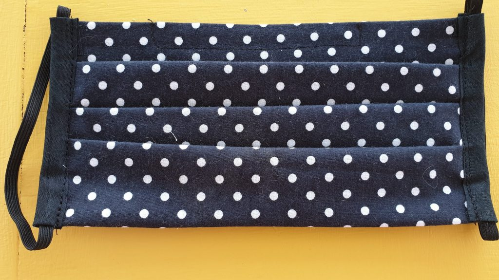 Black face covering with small white polka dots